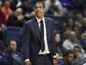 """FILE - In this Dec. 9, 2017 file photo, Connecticut head coach Kevin Ollie looks up at the scoreboard during the first half of an NCAA college basketball game against Coppin State in Storrs, Conn. UConn has fired Ollie, with the team under NCAA investigation and the Huskies having completed their second straight losing season. The university said in a statement Saturday, March 10, 2018,  it has """"initiated disciplinary procedures"""" to dismiss him for """"just cause."""" The school says it would have no further comment until its """"disciplinary process"""" and the ongoing NCAA inquiry are complete."""