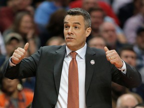 FILE - In this March 16, 2018, file photo, Virginia coach Tony Bennett signals for a jump ball during the first half of the team's first-round game against UMBC in a men's college basketball tournament in Charlotte, N.C. Bennett was named The Associated Press NCAA college basketball Coach of the Year, Thursday, March 29, 2018.