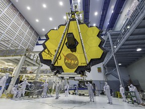 In this April 13, 2017 photo provided by NASA, technicians lift the mirror of the James Webb Space Telescope using a crane at the Goddard Space Flight Center in Greenbelt, Md. The telescope's 18-segmented gold mirror is specially designed to capture infrared light from the first galaxies that formed in the early universe. On Tuesday, March 27, 2018, NASA announced it has delayed the launch of the next-generation space telescope until 2020.