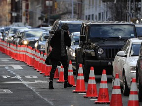 A pedestrian cuts between cars waiting in line during rush hour traffic on Hudson Street near the entrance to the Holland Tunnel, Friday, March 16, 2018, in New York. Prospects appear to be dimming for the latest proposal to impose new tolls on motorists entering the busiest parts of Manhattan. A state panel recommended tolls of as much as $11 or more as a way to address gridlock while raising money for transit. But lawmakers are balking, with some suggesting a more limited fee for taxis, limos and ride-hailing services like Uber instead.