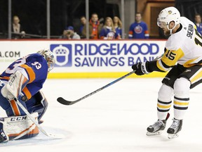 New York Islanders goaltender Christopher Gibson (33) of Finland makes a save on a shot by Pittsburgh Penguins center Riley Sheahan (15) during the first period of an NHL hockey game in New York, Tuesday, March 20, 2018.