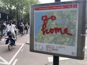 """FILE - In this May 11, 2016, file photo, graffiti reading """"Go Home"""" is sprayed on a map of bicycle paths at the entrance to Amsterdam's Vondelpark, a popular spot for tourists to ride their rental bicycles. Experts from GetYourGuide say travelers can reduce their impact on heavily touristed sites by booking visits in advance for less popular times, by traveling in off-peak seasons and by seeking out smaller, more authentic experiences where they can live like a local."""