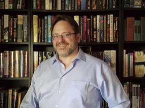 """In this undated photo Nathan Shafer, a life-long book collector, poses in front of his bookshelf in Arvada, Colo. Shafer said he feels there is no point to a backwards-facing bookshelf. """"That's not what books are for,"""" he said."""