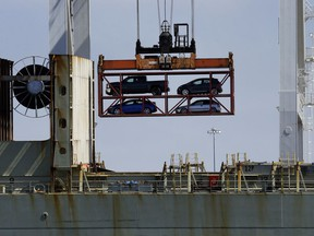 FILE - In this July 13, 2017, file photo, a crane transporting vehicles operates on a container ship at the Port of Oakland, in Oakland, Calif. The Trump administration said Tuesday, March 27, 2018, it has widened U.S. access to South Korea's car market while providing American manufacturers protection from South Korean imports.
