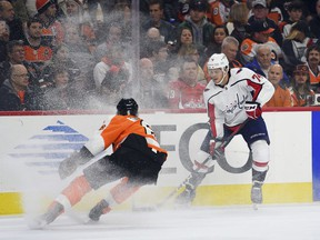 Washington Capitals' John Carlson, right, controls the puck past Philadelphia Flyers' Travis Sanheim during the first period of an NHL hockey game, Sunday, March 18, 2018, in Philadelphia.