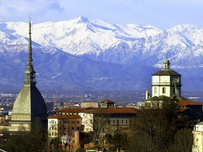 FILE - In this Feb. 20, 2006 file photo, the Mole Antoneliana, left, Turin's most famous landmark, is backdropped by the Alps, in Turin, northern Italy. The Italian Olympic Committee sent a letter of intent to the IOC on Thursday, March 29, 2018, stating its plans of combining Milan and Turin to bid for the 2026 Winter Olympics.