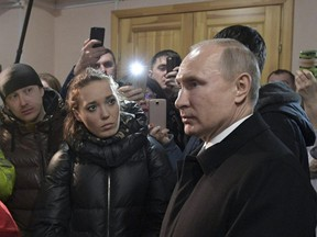 Russian President Vladimir Putin listens to locals and relatives of the victims of a fire in a multi-story shopping centre in the Siberian city of Kemerovo, about 3,000 kilometres east of Moscow, Russia, Tuesday, March 27, 2018.