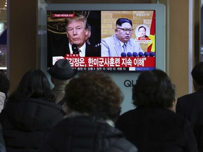 """People watch a TV screen showing North Korean leader Kim Jong Un and U.S. President Donald Trump, left, at the Seoul Railway Station in Seoul, South Korea, Friday, March 9, 2018. After months of trading insults and threats of nuclear annihilation, Trump agreed to meet with North Korean leader Kim Jung Un by the end of May to negotiate an end to Pyongyang's nuclear weapons program, South Korean and U.S. officials said Thursday. No sitting American president has ever met with a North Korea leader. The signs read: """" Kim Jong Un understands that the routine joint military exercises between the South Korean and the United States must continue."""""""