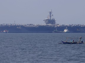 In this Feb. 17, 2018, file photo, fishermen on board a small boat pass by the USS Carl Vinson aircraft carrier at anchor off Manila, Philippines, for a five-day port call.