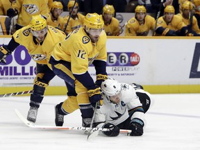 San Jose Sharks center Joe Pavelski (8) falls as he chases the puck with Nashville Predators center Mike Fisher (12) and right wing Ryan Hartman (38) in the first period of an NHL hockey game Thursday, March 29, 2018, in Nashville, Tenn.