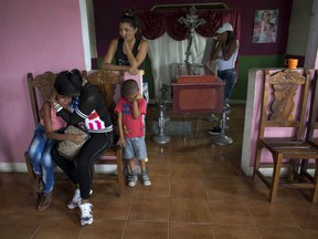 """The coffin with the remains of Daniel Marquez sits in his living room as his daughter Feliana, 13, left, is consoled by her aunt Sorangel Gutierrez, in Valencia, Venezuela, Thursday, March 29, 2018. Marquez is one of 68 people killed in a fire that swept through a Venezuelan police station jail Wednesday. """"He didn't deserve to die like this,"""" Gutierrez, Marquez's sister-in-law, said as relatives wept before his casket."""