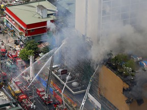 Firemen battle a fire that engulfs the Manila Pavilion Hotel and Casino Sunday, March 18, 2018 in Manila, Philippines. A fire hit the hotel, where more than 300 guests were evacuated, some by helicopter.