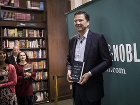 """Former FBI Director James Comey poses for photographs as he arrives to speak about his new book """"A Higher Loyalty: Truth, Lies, and Leadership"""" at Barnes & Noble bookstore, April 18, 2018 in New York City."""