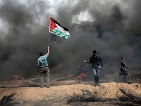 """A Palestinian protester waves the national flag as smoke billows from a tire fire during clashes with Israeli forces on April 20, 2018, east of Khan Yunis, in the southern Gaza Strip during mass protests along the border of the Palestinian enclave, dubbed """"The Great March of Return,"""" which has the backing of Gaza's Islamist rulers Hamas."""
