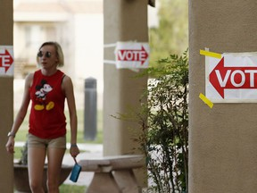 A voter leaves a polling station after casting a vote as Democratic candidate Dr. Hiral Tipirneni and Republican Debbie Lesko look to fill the CD8 seat vacated by Republican Rep. Trent Franks in a special election, Tuesday, April 24, 2018, in Glendale, Ariz.