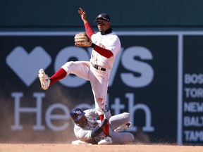 Boston Red Sox shortstop Xander Bogaerts and Tampa Bay Rays' Denard Span look down to first to watch after Bogaerts completed a double play during the eighth inning of Boston's 10-3 win in a baseball game at Fenway Park in Boston Saturday, April 7, 2018.