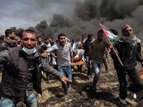 An injured Palestinian protestor is carried by fellow demonstrators during clashes with Israeli security forces near the border with Israel, east of Khan Yunis, in the southern Gaza Strip, on Friday, April 6, 2018.