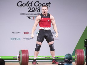 Canada's Boady Santavy reacts after lifting 196kg in the clean and jerk on his way to a silver medal in the men's 94kg weightlifting finals at the Commonwealth Games Sunday, April 8, 2018 in Gold Coast, Australia.
