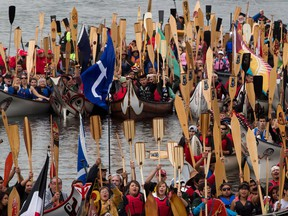 Paddlers raise their paddles as they gather on Vancouver's False Creek during an all nations canoe gathering held as part of Reconciliation Week in Vancouver, B.C., on Tuesday September 17, 2013.