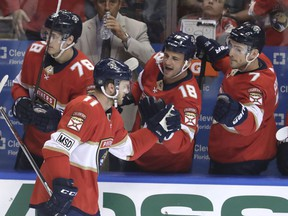 Florida Panthers' Jonathan Huberdeau, left, celebrates with Micheal Haley (18) and Colton Sceviour (7) after scoring a goal during the first period of an NHL hockey game against the Buffalo Sabres, Saturday, April 7, 2018, in Sunrise, Fla.