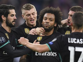 Madrid's Marcelo, center,  is congratulated by his teammates after scoring his side's first goal during the soccer Champions League first leg semifinal soccer match between FC Bayern Munich and Real Madrid in Munich, southern Germany, Wednesday, April 25, 2018.