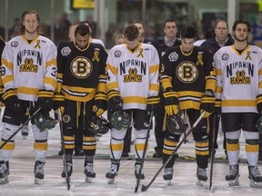 In this April 14 file photo, Nipawin Hawks and Estevan Bruins players pause for a moment of silence to acknowledge first responders, victims, and survivors of the bus crash that killed 16 members of the Humboldt Broncos.