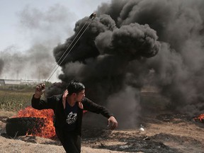 A Palestinian hurls stones at Israeli troops during a protest at the Gaza Strip's border with Israel on Friday, April 6, 2018.