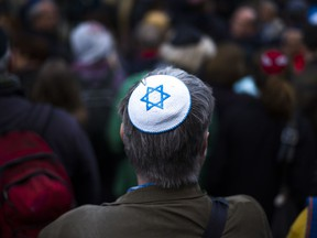 A man wears a Jewish skullcap, as he attends a demonstration against an anti-Semitic attack  in Berlin, Wednesday, April 25, 2018. Germans of various faiths donned Jewish skullcaps and took to the streets Wednesday in several cities to protest an anti-Semitic attack in Berlin and express fears about growing hatred of Jews in the country.