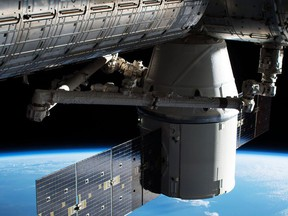 In this image provided by NASA, the Dragon capsule arrives at the International Space Station on Wednesday, April 4, 2018 with food and experiments. It will remain attached to the orbiting outpost for about a month, returning to Earth in May. Dragon launched Monday from Cape Canaveral, Florida, aboard a used Falcon rocket. SpaceX wants to reduce launch costs by recycling rocket parts.  (NASA via AP)