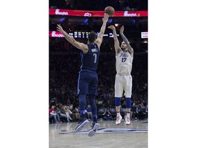 Philadelphia 76ers' JJ Redick, right, shoots the three-point basket as Dallas Mavericks' Dwight Powell, left, defends during the second half of an NBA basketball game Sunday, April 8, 2018, in Philadelphia.