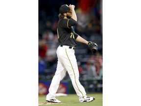 Pittsburgh Pirates relief pitcher George Kontos tugs his cap after giving up a three-run-homer to Cincinnati Reds' Eugenio Suarez in the eighth inning of a baseball game, Saturday, April 7, 2018, in Pittsburgh.