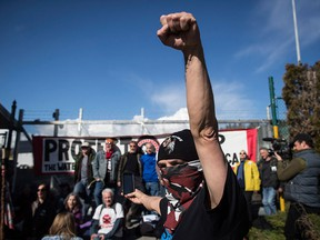 A protester raises his fist as others block a gate outside Kinder Morgan in Burnaby, B.C. on March 17, 2018.