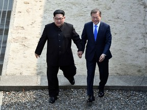 North Korean leader Kim Jong Un, left, and South Korean President Moon Jae-in cross the military demarcation line at the border village of Panmunjom in Demilitarized Zone Friday, April 27, 2018.