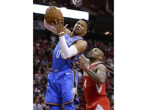 Oklahoma City Thunder guard Russell Westbrook (0) pulls down a rebound in front of Houston Rockets forward PJ Tucker (4) during the first half of an NBA basketball game Saturday, April 7, 2018, in Houston.