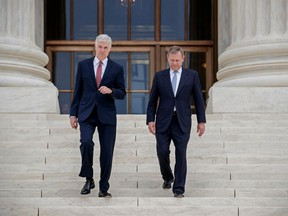 FILE - In this June 15, 2017, file photo, Associate Supreme Court Justice Neil Gorsuch, left, joined by Chief Justice John Roberts, walks down the steps of Supreme Court in Washington, following Gorsuch investiture, a ceremony to mark his ascension to the bench. Gorsuch became the Supreme Court's newest member a year ago on April 10, 2017 . President Donald Trump's pick to replace the late Justice Antonin Scalia has now heared more than 60 cases on issues including gerrymandering, union fees, cellphone and data privacy and gambling on sports. He's written his first Supreme Court opinions but also dealt with his first complaint as a member of the court's cafeteria committee.