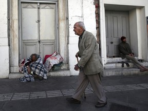 An elderly man passes by homeless men in Athens, Monday, April 23, 2018. Greece has beaten its bailout budget targets for a third successive year and eased its massive debt burden by a fraction as the country prepares to exit its international rescue program in four months.