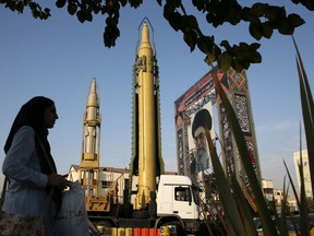 A Ghadr-H missile, centre, a solid-fuel surface-to-surface Sejjil missile and a portrait of Supreme Leader Ayatollah Ali Khamenei are displayed at Baharestan Square in Tehran, Iran, in a Sept. 24, 2017 file photo.