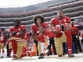 In this Oct. 2, 2016 file photo, from left, San Francisco 49ers outside linebacker Eli Harold, quarterback Colin Kaepernick and safety Eric Reid kneel during the national anthem before a game against the Dallas Cowboys.