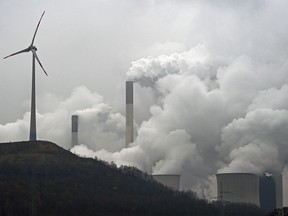 In this file photo dated Monday, Dec. 1, 2014, a wind turbine overlooks the coal-fired power station in Gelsenkirchen, Germany.