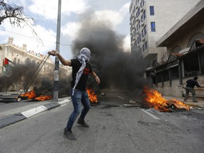 Palestinians sling stones during clashes with Israeli troops following a protest against the U.S. decision to relocate it's Israeli embassy to Jerusalem, in the West Bank city of Bethlehem, Monday, May 14, 2018.