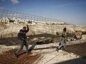 """FILE - In this Jan. 22, 2017 file photo, workers carry material at a construction site in the West Bank settlement of Maaleh Adumim. Israeli Defense Minister Avigdor Lieberman said Thursday, May 24, 2018, that he will seek approval next week to fast-track construction of 2,500 new West Bank settlement homes this year and advance 1,400 more units that are currently in the planning stage. Senior Palestinian official Hanan Ashrawi condemned Lieberman's announcement as """"Israeli colonialism, expansionism and lawlessness"""" and called on the International Criminal Court in The Hague, Netherlands, to launch an investigation."""