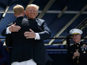 President Donald Trump embraces the last graduate in line during a graduation and commissioning ceremony at the U.S. Naval Academy, Friday, May 25, 2018, in Annapolis, Md.