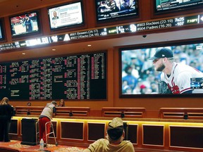 FILE - In this Monday, May 14, 2018 file photo, people make bets in the sports book area of the South Point Hotel and Casino in Las Vegas. Those who deal with compulsive gambling are worried that a rapid expansion of sports betting in the U.S. could cause more people to develop gambling problems. The U.S. Supreme Court on Monday cleared the way for states to legalize sports betting.