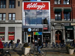 FILE- In this Dec. 14, 2017, file photo, people bike and walk by Kellogg's NYC Cafe at Union Square in New York. Kellogg Co. reports earnings Thursday, May 3, 2018.