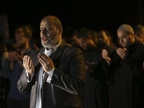 Hamas leader Khalil al-Hayya leads an evening prayer called 'tarawih' marking the first eve of the holy fasting month of Ramadan, outside the tents of the protest camp near the Israeli border east of Gaza City, Wednesday, May 16, 2018.