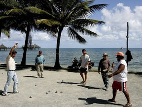 """FILE - In this Thursday, Sept. 22, 2005 file photo, locals on the beach in Noumea, New Caledonia, play the traditional ball game """"petanque"""".  French President Emmanuel Macron starts Thursday a highly symbolic visit to New Caledonia, a French territory in the South Pacific which is getting ready to vote in a self-determination referendum to decide on its own sovereignty."""