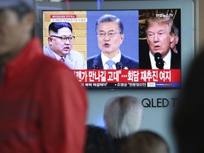 """A TV screen shows images of U.S. President Donald Trump, right, South Korean President Moon Jae-in and North Korean leader Kim Jong Un, left, during a news program at the Seoul Railway Station in Seoul, South Korea, Friday, May 25, 2018. North Korea said Friday that it's still willing to sit down for talks with the United States """"at any time, at any format"""" just hours after President Donald Trump abruptly canceled his planned summit with the North's leader Kim Jong Un. The signs read """" Hope to see you again someday."""""""