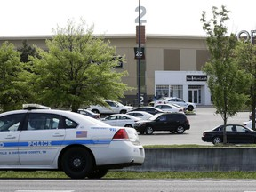 A police car sits outside Opry Mills mall Thursday, May 3, 2018, in Nashville, Tenn. Nashville police said a suspect was taken into custody after a person was shot inside the mall. The mall was evacuated after the gunfire was reported. One person was taken to a hospital and was reported to be in critical condition.