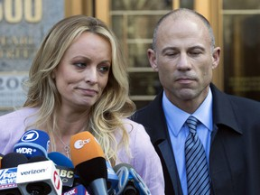 FILE - In this April 16, 2018, file photo, adult film actress Stormy Daniels, left, stands with her lawyer Michael Avenatti as she speaks outside federal court in New York. The story told by President Donald Trump and the White House about payments made to Daniels has evolved over time. The White House has consistently denied Trump had an affair with Daniels, but statements from the president and his aides about a hush money payment made just before the 2016 election have changed.