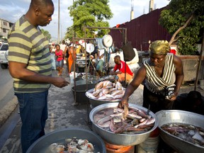 In this April 29, 2018 photo, a fish vendor picks out fish for her client at the biggest fish market in Port-au-Prince, Haiti. The capital's main fish market opens as early as 3am, selling local fish from all over the island's coasts.